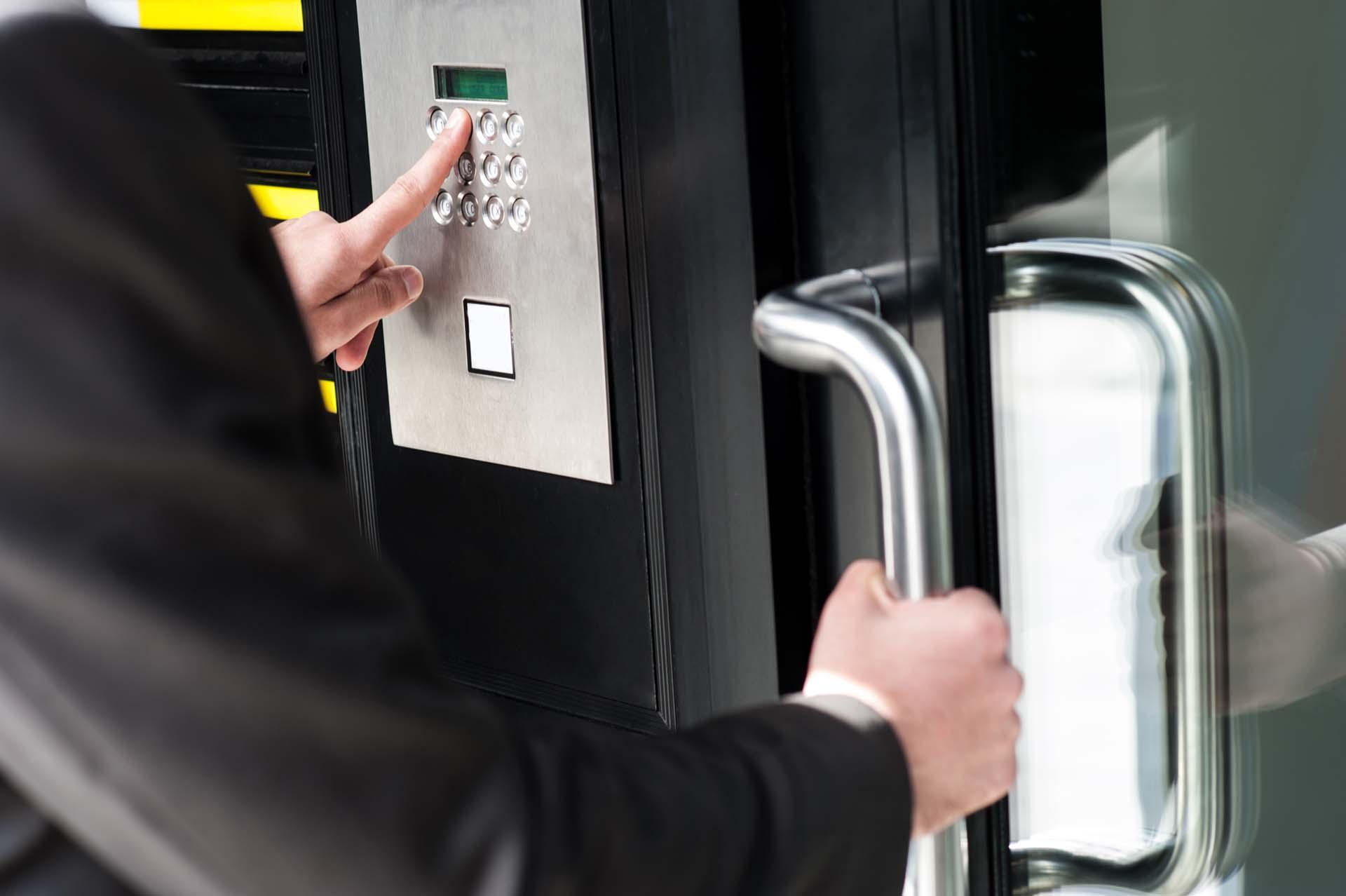Person öffnet eine Tür mit einem elektronischen Zutrittsystem